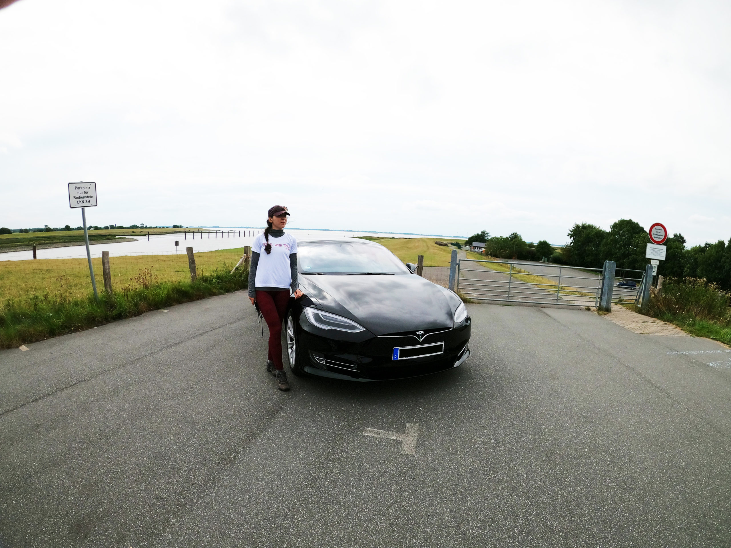 Mihaela from Move more. Eat more and the Tesla Model S near the flood barrier on the river Stör