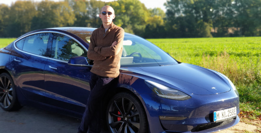 Blue Tesla Model 3 Performance against a field of green
