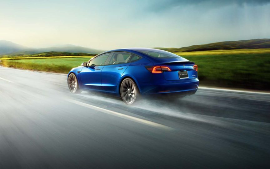 Blue Tesla Model 3 on the road with a green and yellow field in the background
