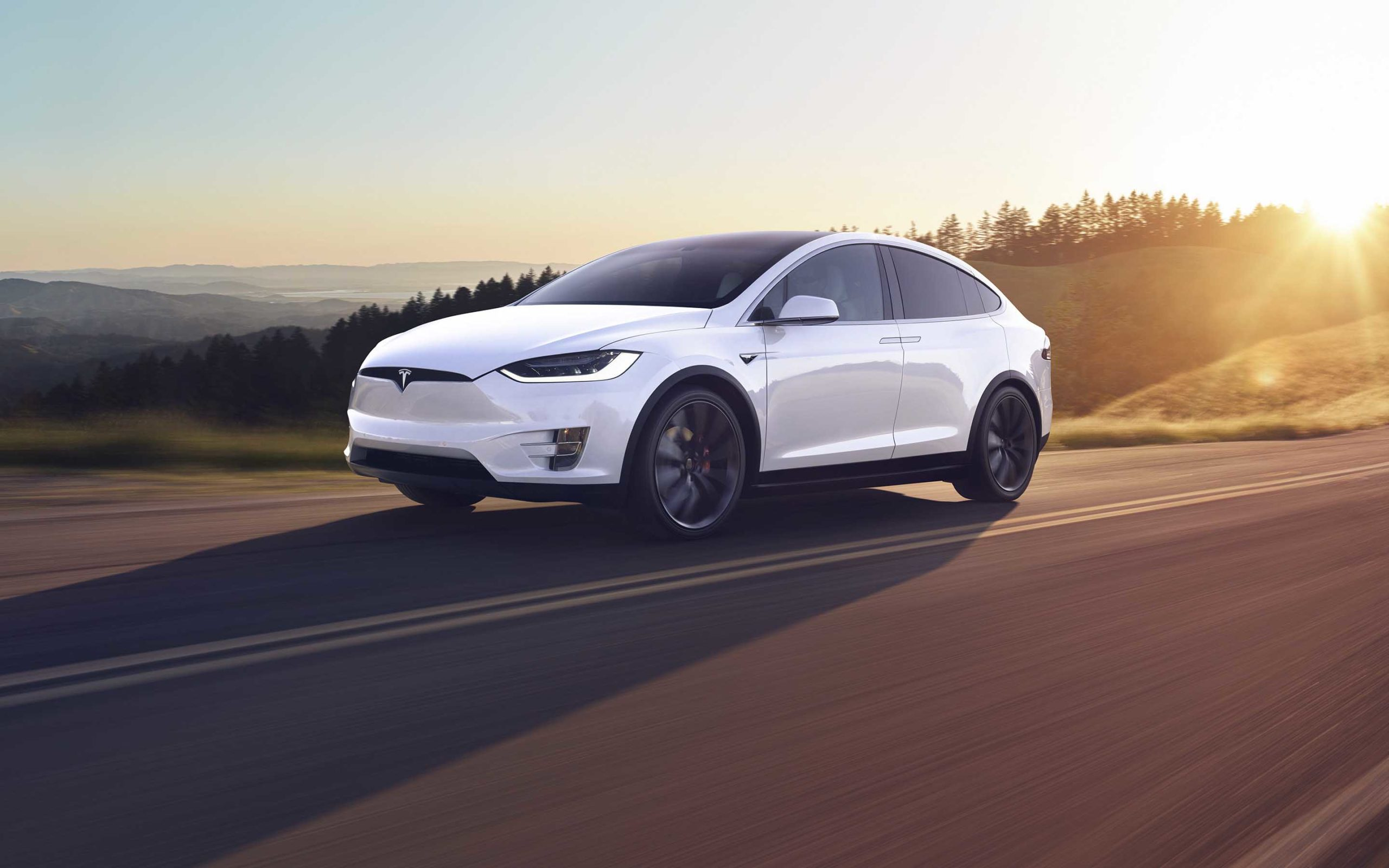 Tesla Model X pearl white on the road with the sunset behind it